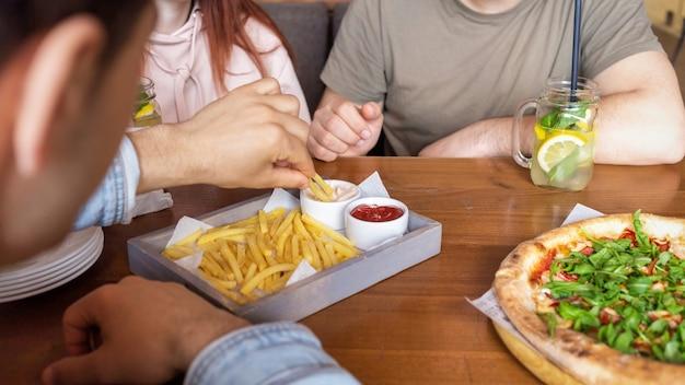 Un groupe d'amis se reposant dans un pub. manger, boire, manger sur la table. amitié
