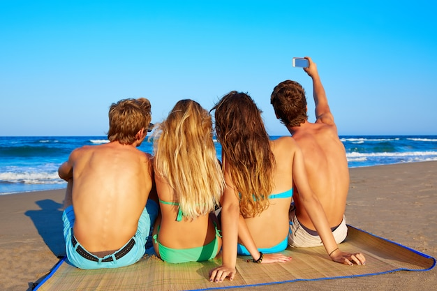 Groupe d'amis selfie photo assis dans le sable de la plage