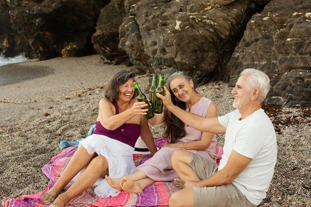 Groupe d'amis seniors applaudissant avec de la bière à la plage