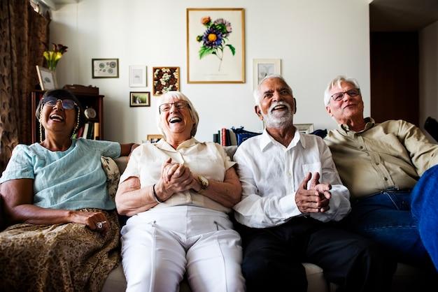 Groupe d'amis seniors assis et regardant la télévision ensemble