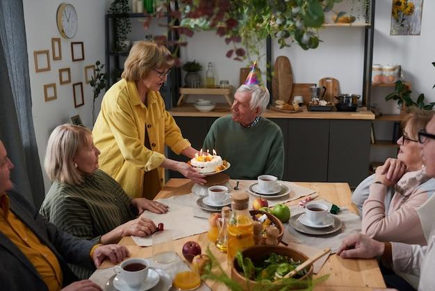 Groupe d'amis seniors célébrant l'anniversaire avec un gâteau ensemble à la table à la maison