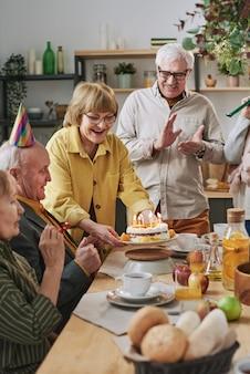 Groupe d'amis seniors célébrant leur anniversaire avec un gâteau avec des bougies assis à table à manger ensemble à la maison