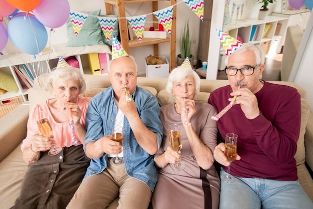 Groupe d'amis seniors ou deux couples avec champagne soufflant des sifflets à la fête d'anniversaire