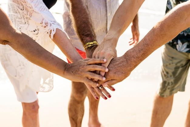 Groupe d'amis seniors empilant les mains