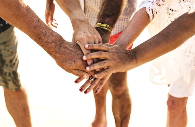 Groupe d'amis seniors empiler des mains
