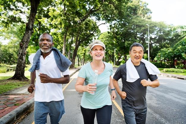 Groupe d'amis seniors jogging ensemble dans un parc