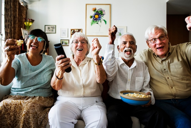 Groupe d'amis seniors joyeux assis et regardant la télévision ensemble