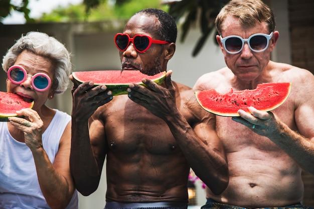 Groupe d'amis seniors manger de la pastèque au bord de la piscine