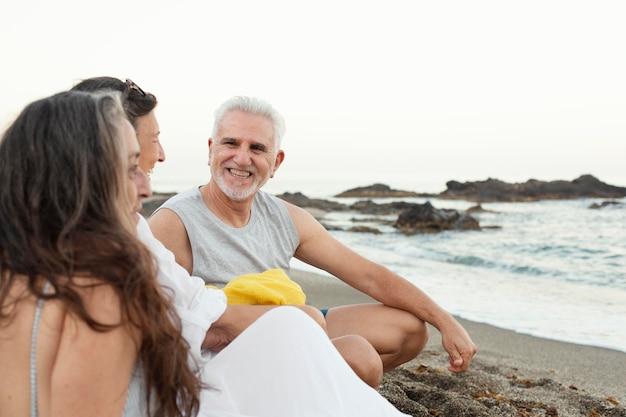Groupe d'amis seniors passant du temps ensemble à la plage