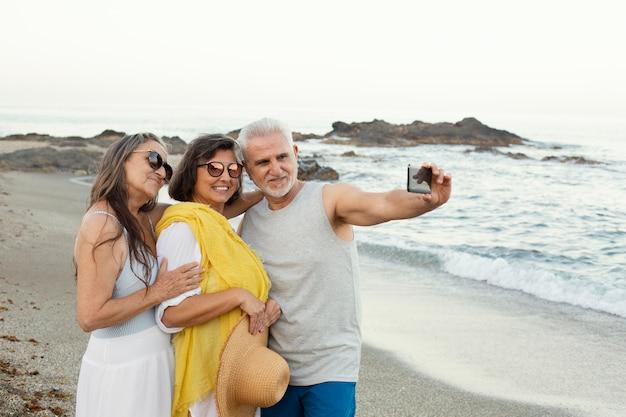 Groupe d'amis seniors prenant selfie avec smartphone sur la plage