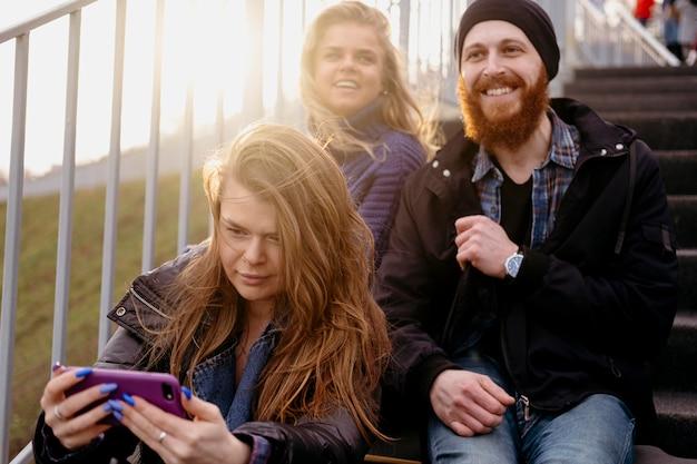 Groupe d'amis avec smartphone dans les escaliers