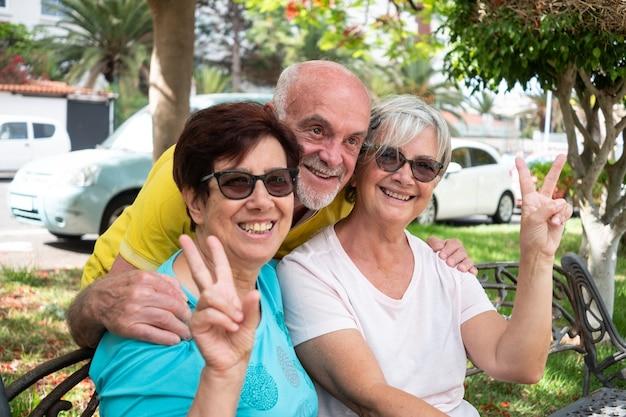 Groupe d'amis souriant assis sur un banc dans le parc. jardin verdoyant, jour d'été. trois personnes âgées de race blanche gesticulant un message, tout va bien.