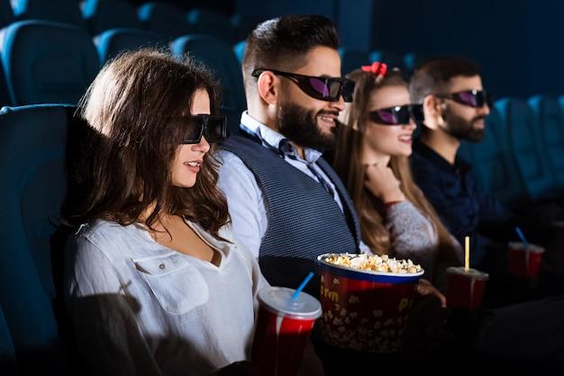 Groupe d'amis souriant joyeusement tout en regardant un film 3d ensemble