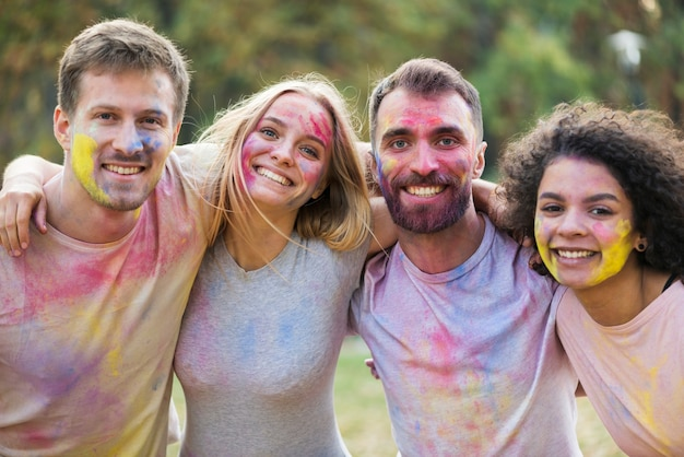 Groupe d'amis souriant et posant avec des visages peints au festival