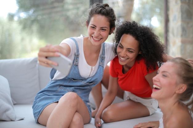 Groupe d'amis souriant tout en prenant un selfie et assis à l'intérieur