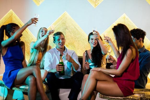 Groupe d'amis souriants assis sur un canapé et griller un verre de champagne
