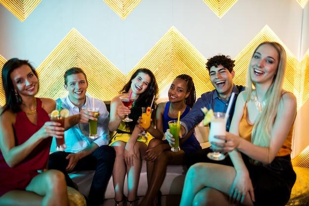 Groupe d'amis souriants assis sur un canapé et montrant un verre de cocktail