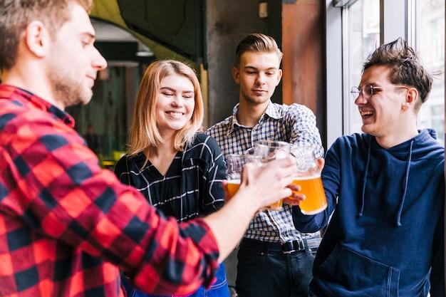 Groupe d'amis souriants portant un toast aux verres de bière