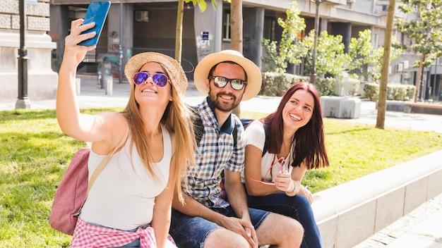 Groupe d'amis souriants prenant selfie sur téléphone portable