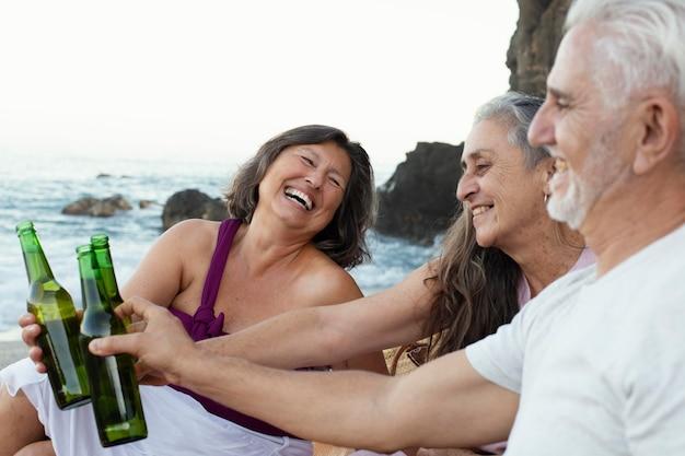 Groupe d'amis supérieurs ayant des bières sur la plage
