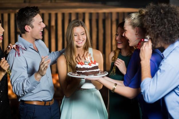 Groupe d'amis surprenant une femme avec un gâteau d'anniversaire