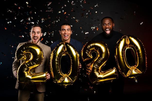 Groupe d'amis tenant des ballons à la fête du nouvel an
