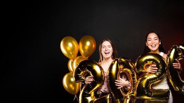 Groupe d'amis tenant des ballons d'or pour le nouvel an