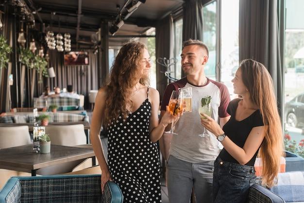 Groupe d'amis tenant différents types de boissons alcoolisées au restaurant
