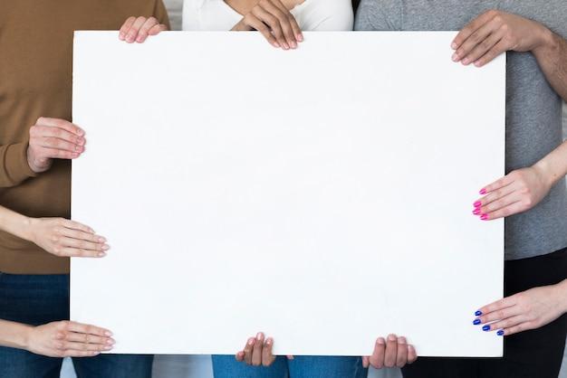 Groupe d'amis tenant une pancarte ensemble