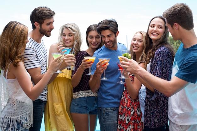 Groupe d'amis tenant un verre de cocktail au bord de la piscine