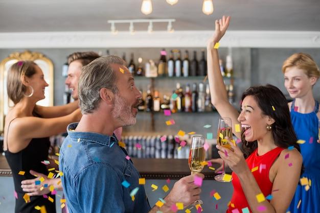 Groupe d'amis tenant un verre de flûte à champagne en dansant
