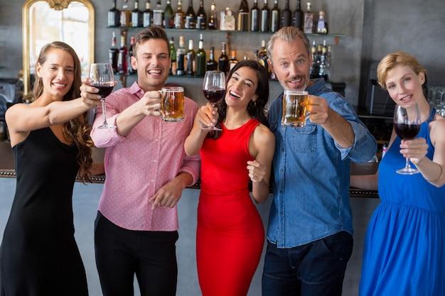 Groupe d'amis tenant des verres de bière et de vin
