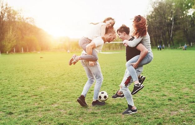 Un groupe d'amis en tenue décontractée joue au soccer en plein air. les gens s'amusent et s'amusent. repos actif et coucher de soleil pittoresque.
