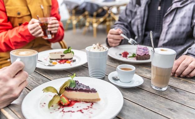 Un groupe d'amis sur une terrasse de restaurant en hiver pendant la quarantaine covid-19. cheesecakes et cafés chauds appréciés par des amis assis autour de la table du café.