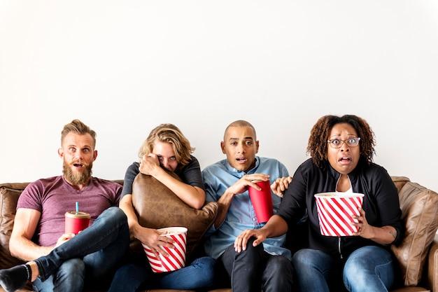 Groupe d'amis terrifiés en regardant un film de thriller