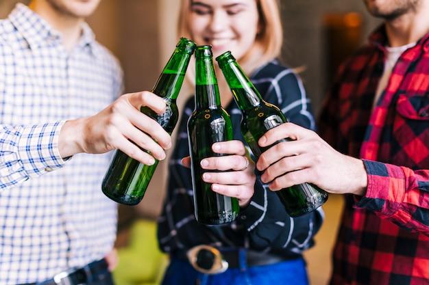 Groupe d'amis tintant des bouteilles de bière dans le pub