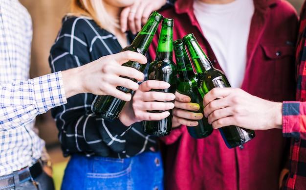 Groupe d'amis tintant des bouteilles de bière