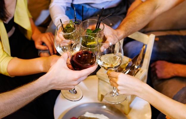 Un groupe d'amis tintent des verres avec des boissons au café. ils discutent et s'amusent