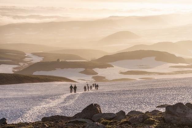 Groupe d'amis ou de touristes se tient au point de vue des montagnes.