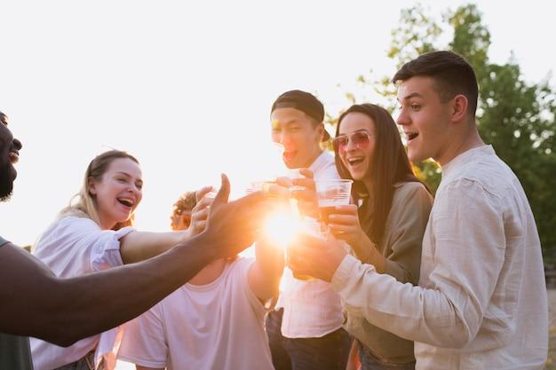 Groupe d'amis trinquant à bière pendant le pique-nique à la plage. mode de vie, amitié, s'amuser, week-end et concept de repos.