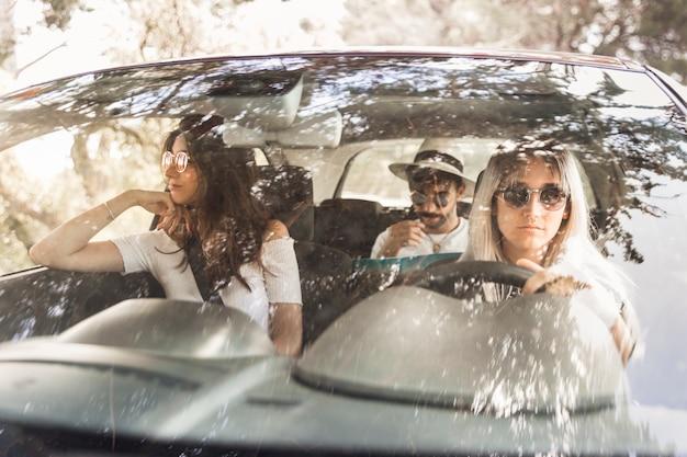 Groupe d'amis voyageant en voiture de luxe