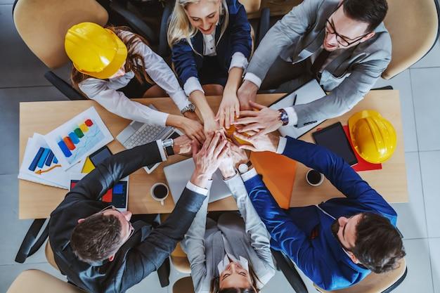 Groupe d'architectes dévoués qui travaillent dur empiler les mains alors qu'il était assis à table dans la salle de conférence. travail en équipe.