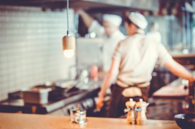 Groupe d'arrière-plan flou de chefs cuisinant dans la cuisine