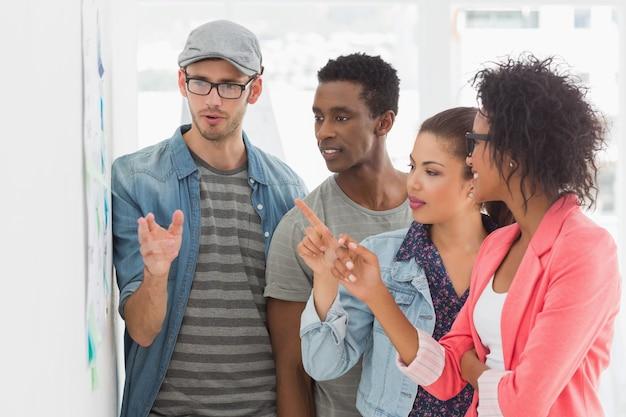 Groupe d'artistes en discussion devant le tableau blanc au bureau