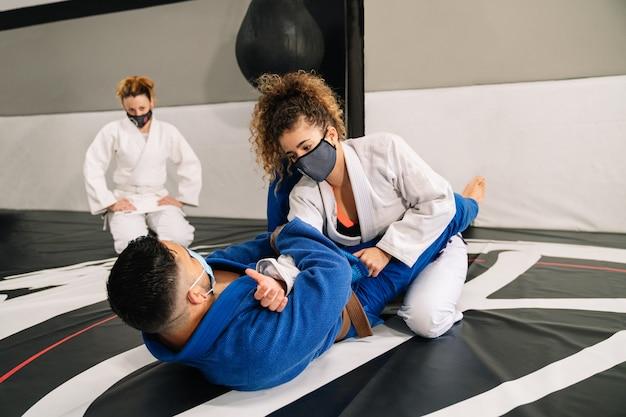 Groupe d'arts martiaux et de judo avec des kimonos sur le tapis de sol du gymnase avec un étudiant les regardant tous porter un masque à cause du covid 19