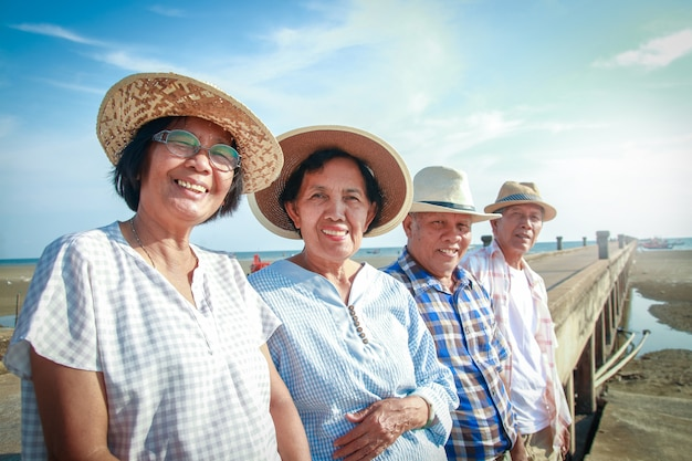 Un groupe asiatique âgé sourit au pont en béton au bord de la mer, heureux après sa retraite.