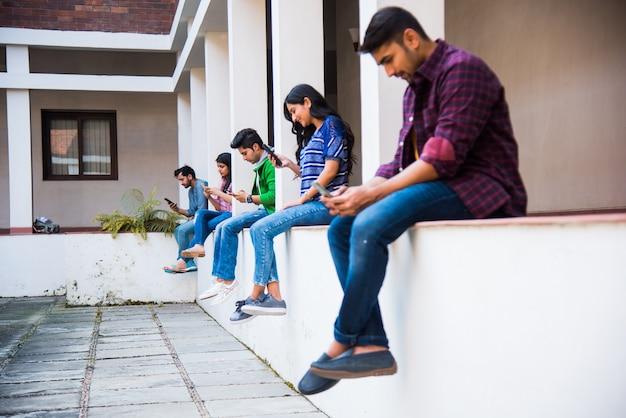 Groupe asiatique indien d'étudiants utilisant des smartphones pour les médias sociaux, envoyer des sms, regarder des vidéos