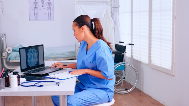 Groupe d'assistants travaillant dans le bureau de l'hôpital, analysant la radiographie numérique du cerveau et le scanner corporel. médecin en médecine rédige une liste uniforme de patients consultés et diagnostiqués, faisant des recherches.
