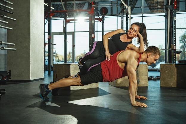 Un groupe d'athlètes musclés faisant de l'exercice au gymnase. gymnastique, entraînement, flexibilité d'entraînement de fitness. mode de vie actif et sain, jeunesse, musculation. entraînement haut et bas du corps. soutien.