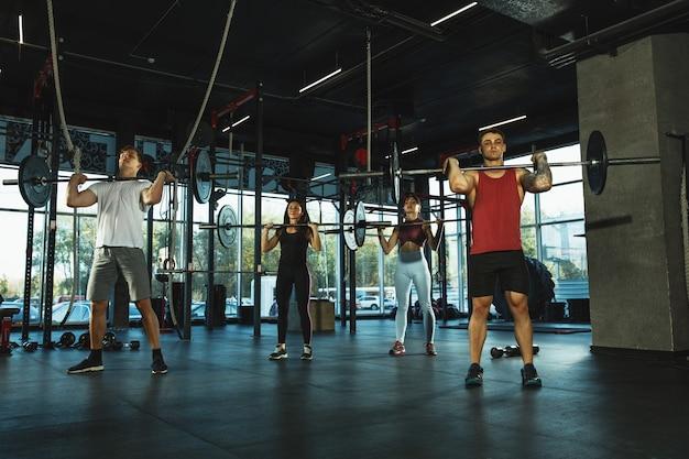 Un groupe d'athlètes musclés faisant de l'exercice au gymnase. gymnastique, entraînement, flexibilité d'entraînement de fitness. mode de vie actif et sain, jeunesse, musculation. s'entraîner avec des poids, faire des squats.